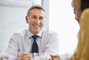Smiling mature businessman with colleagues in meeting at board room